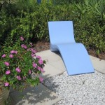 A whimsical blue bench in a private space comfortably curves for lying down amidst the flora.