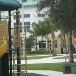 The playground is surrounded by canopy trees that provide shade.